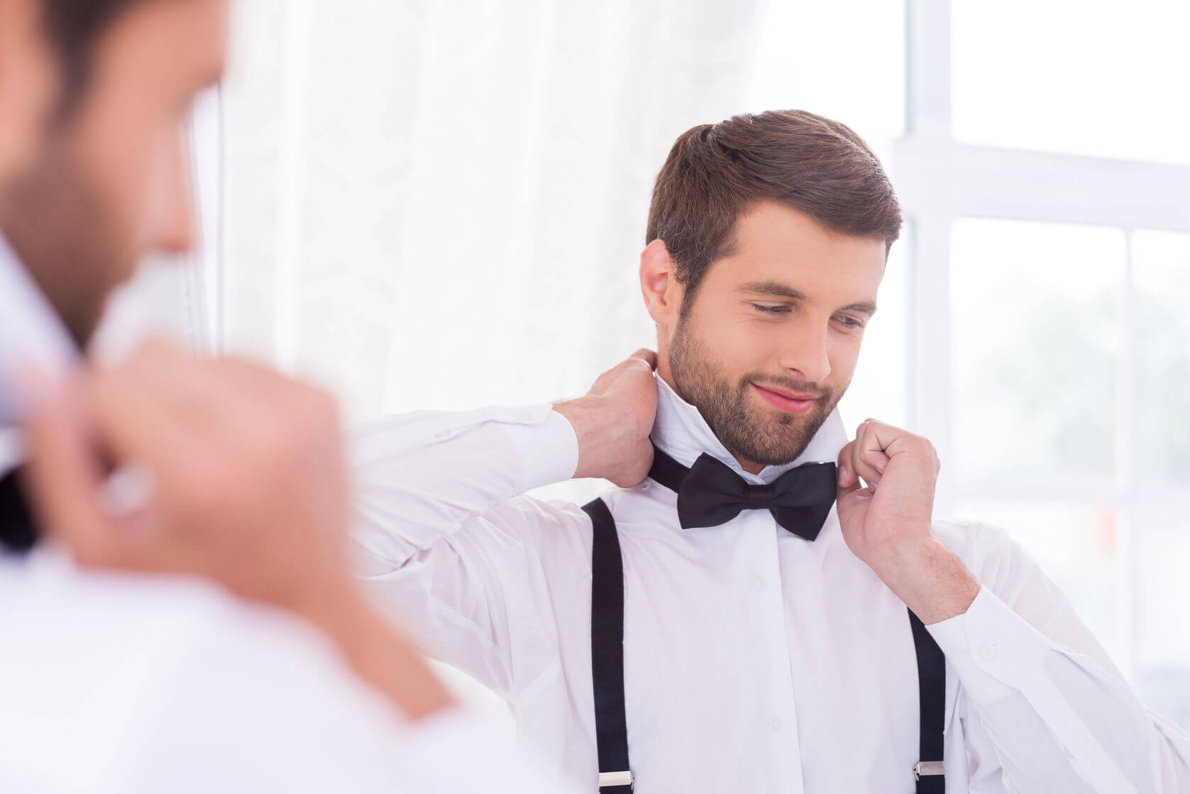 best man smiling at the mirror