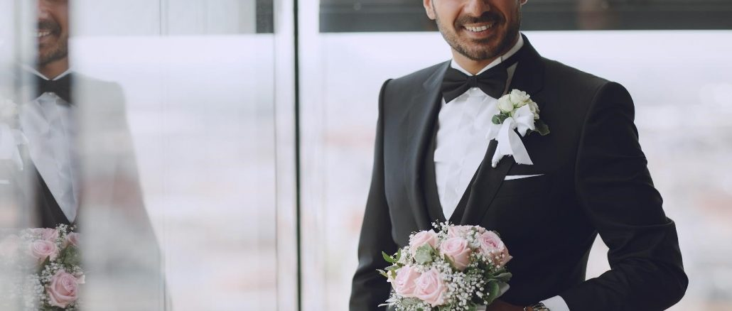 smiling groom holiding a bouquet